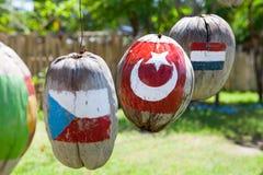 Många flaggor av länder målade på kokosnötterna arkivfoton