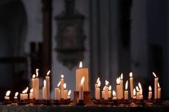 Många flammor på stearinljus som tänds i kyrkan i respekt Kristendomen royaltyfri foto