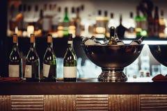 Många flaskor av vin i metallen bowlar på stången Royaltyfri Bild
