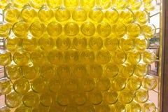 Många flaskor för vitt vin som staplas densly i en stor bur under pr Royaltyfri Bild