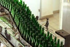 Många flaskor på transportbandet royaltyfri fotografi