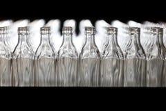 Många flaskor på transportbandet i glasbruk arkivfoto