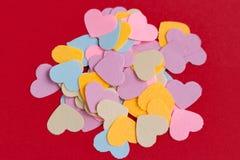 Många formade färgrik pappers- hjärta konfettier på rosa eller röd bakgrund Valentin begreppskort arkivbild