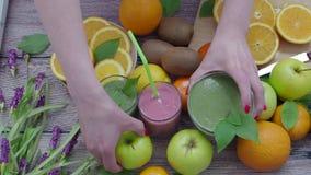 Många frukter och bär- och grönsaksmoothies på tabellen stock video