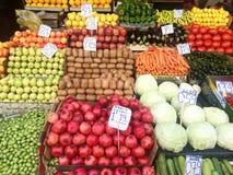 Många frukter och grönsaker i askar i marknaden med prislappar royaltyfria foton