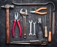 Många funktionsdugliga hjälpmedel på svärtar den konkreta tabellen Pojkar mapp, plattång, rest, hammare, skiftnyckel, skruvmejsel Royaltyfri Foto