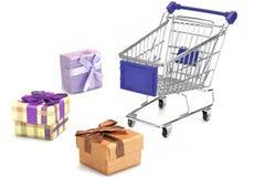 Många gåvaask och tom shoppingvagn som isoleras på vit Royaltyfri Foto