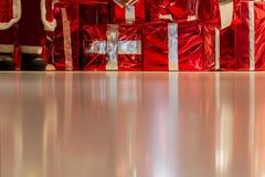 Många gåvaaskar med guld- band- och för jultomten` s fot på skinande bakgrund Jul bakgrund, gåvor, shoping begrepp Royaltyfri Fotografi
