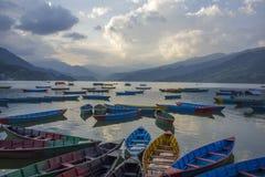 Många gamla blåa gröna gula röda träfartyg på sjön i aftonen mot bakgrunden av bergen fotografering för bildbyråer