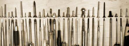 Många gammalmodiga skruvmejslar och olika skruvar Arkivfoto
