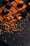 Många godis- och chokladchiper på en svart bakgrund arkivbild