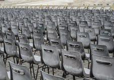 Många gråa stolar i raka linjer på en fyrkant royaltyfri bild