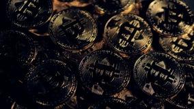 Många guld- bitcoins ligger under det dunkla ljuset stock video