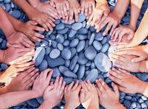 Många händer för barn` s i en cirkel på stenarna Royaltyfri Bild