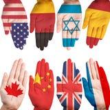 Många händer med olika landsflaggor Arkivfoto