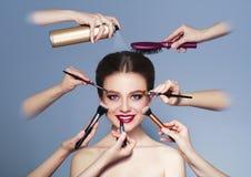 Många händer med skönhetsmedel borstar, skuggor som gör smink Royaltyfri Fotografi