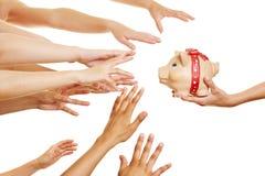 Många händer som når för spargrisen Royaltyfria Bilder