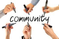 Många händer som skriver gemenskapord Arkivfoton