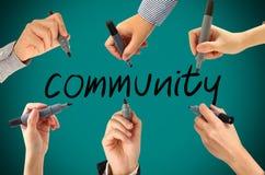 Många händer som skriver gemenskapord Arkivbild
