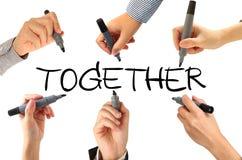 Många händer som tillsammans skriver ord Arkivbild