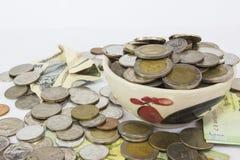 Många hög av myntbahtThailand valuta i gul keramisk bunke Arkivbild