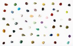 Många halv-dyrbara stenar som är ordnade på vit Arkivbild