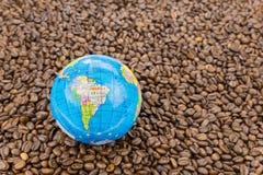 Många hela kaffebönor med Sydamerika på jordklotet Arkivfoton