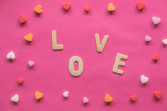 många hjärtor med ordet FÖRÄLSKELSE på rosa bakgrund, förälskelsesymbol, valentin dag, förhållandebegrepp royaltyfri bild
