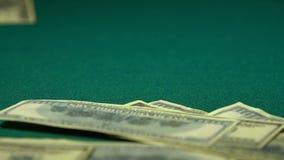 Många hundra-dollar räkningar som faller till den gröna tabellen som segrar stor jackpott, närbild arkivfilmer