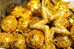 Många julbollar och stjärna i färgrik xmas-bakgrund för guld- paljetter Royaltyfri Foto