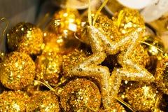 Många julbollar och stjärna i färgrik xmas-bakgrund för guld- paljetter Royaltyfria Foton