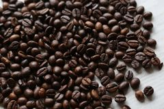 Många kaffebönor på en vit tabell Grillade bönor arkivbild