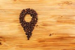 Många kaffebönor på wood bakgrund klämmer fast kaffe Arkivfoto