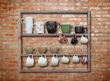 Många kaffekopp på den wood hyllan Royaltyfria Foton