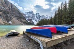 Många kanoter på trädäck på morän sjön i den Banff nationalparken arkivbild