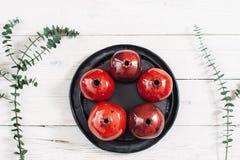 Många keramiska röda granatäpplen och svart platta Arkivbild