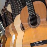 Många klassiska gitarrer som hänger på väggen i shoppa Arkivfoto