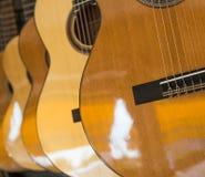 Många klassiska gitarrer som hänger på väggen i shoppa Royaltyfri Bild