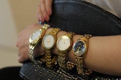 Många klockor flickan har på hennes hand en guld- klocka arkivfoton
