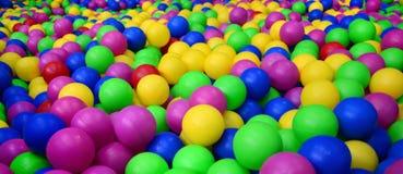 Många klumpa ihop sig färgrik plast- i en kids& x27; ballpit på en lekplats royaltyfri bild