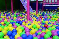 Många klumpa ihop sig färgrik plast- i en kids& x27; ballpit på en lekplats Fotografering för Bildbyråer