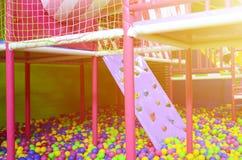 Många klumpa ihop sig färgrik plast- i en kids& x27; ballpit på en lekplats Arkivfoto