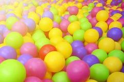 Många klumpa ihop sig färgrik plast- i en kids& x27; ballpit på en lekplats Royaltyfria Foton