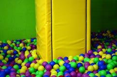 Många klumpa ihop sig färgrik plast- i en kids& x27; ballpit på en lekplats Royaltyfri Fotografi