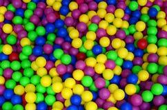 Många klumpa ihop sig färgrik plast- i en kids& x27; ballpit på en lekplats Royaltyfria Bilder