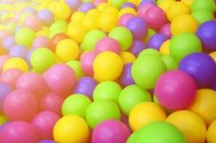 Många klumpa ihop sig färgrik plast- i en kids& x27; ballpit på en lekplats Arkivbilder