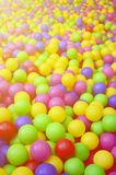 Många klumpa ihop sig färgrik plast- i en kids& x27; ballpit på en lekplats Royaltyfri Foto