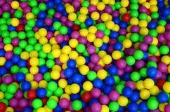 Många klumpa ihop sig färgrik plast- i en kids& x27; ballpit på en lekplats Arkivbild