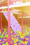 Många klumpa ihop sig färgrik plast- i en kids& x27; ballpit på en lekplats Arkivfoton