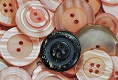 Många knappar för rosa färger och för en svart Arkivbild